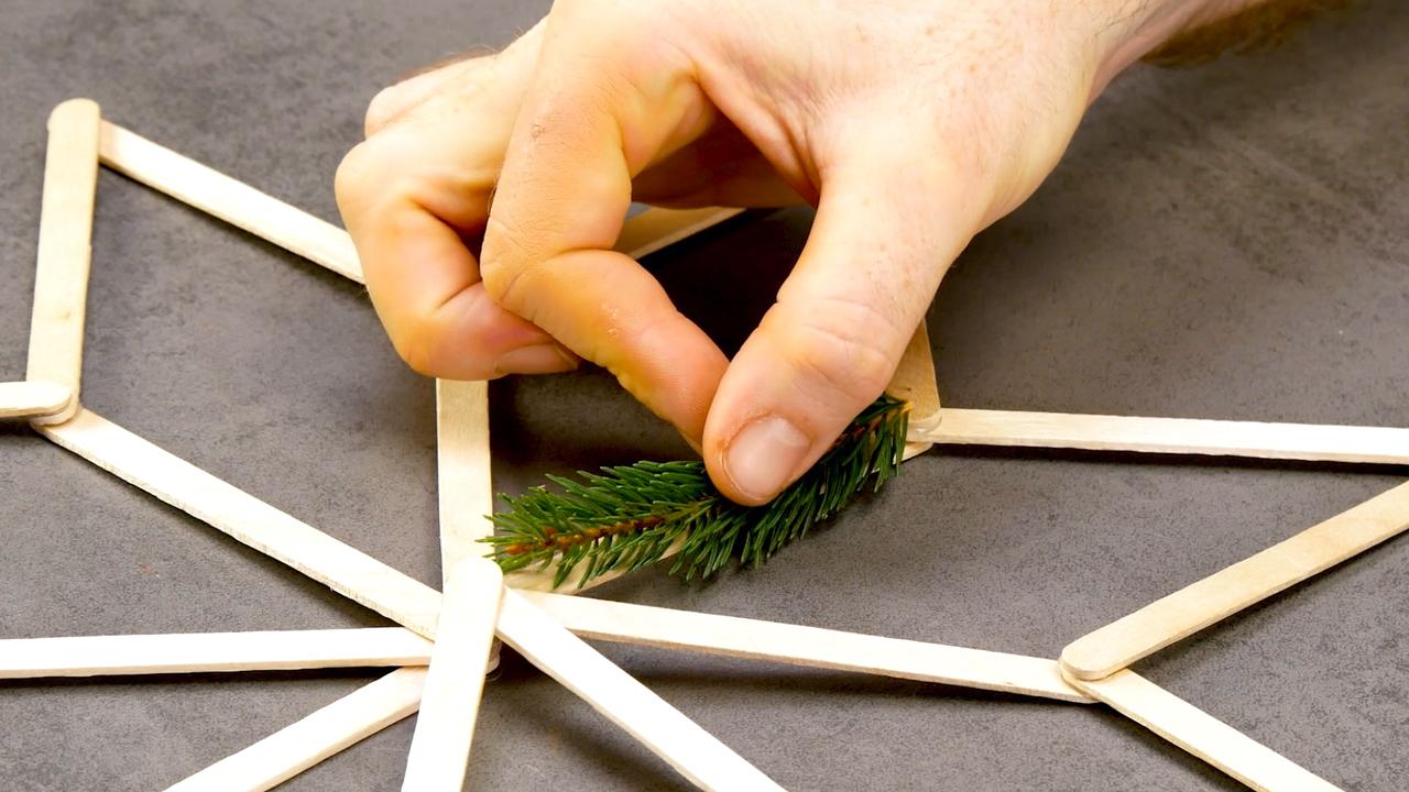 Tannenzweig wird auf Holzstern geklebt